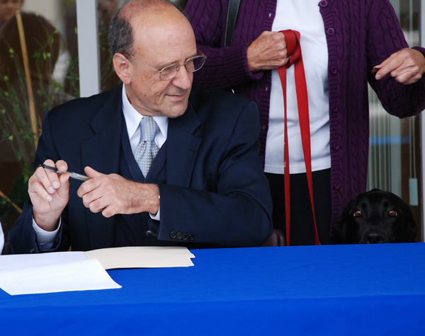 Dora, County Executive Leopold's black Labrador retriever, helps him sign the legislation.