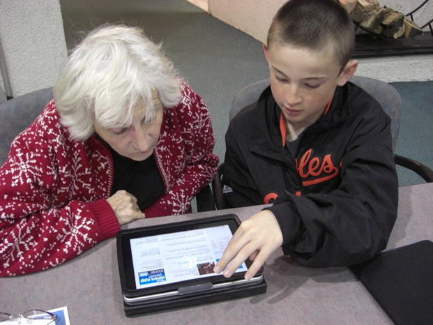 Boy showing woman a computer