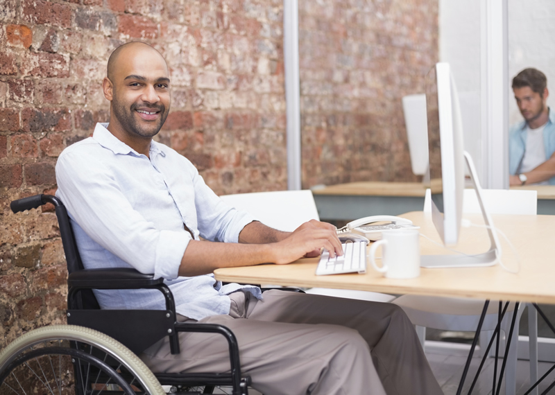 man at a desk working on a laptop in a wheelchair