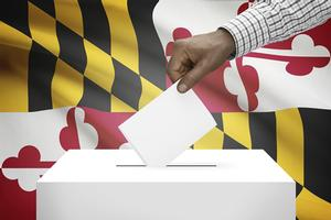 Mans arm casting a ballot in a white box with MD flag behind