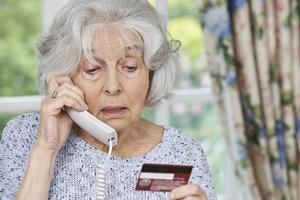 senior citizen giving a credit card over the phone